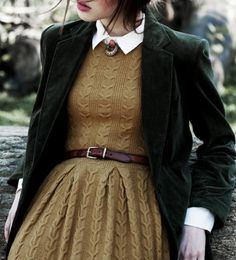 Cable knit dress in a mustard brown with white collar, brown belt, and dark green blazer