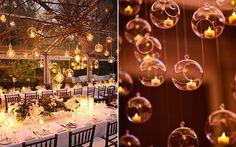 """pequenas velas são colocadas em suportes delicadinhos de vidro e espalhadas pelo salão. Você pode prendê-las no teto com fios de nylon, e isso cria um efeito lindo de """"velas flutuantes""""."""