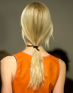 The low-slung ponytail at Reed Krakoff reflected the designer's love of minimalism by having a simple yet sophisticated texture. Lead hairstylist Guido tousled hair with a messy center part and pulled it back into a loose pony tied off with a black leather strap. Striking!