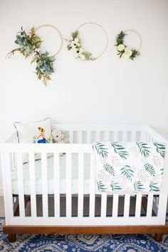 modern crib with whimsical wreath decor
