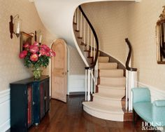 A traditional curved staircase and a rounded doorway accent a Hamptons hallway.