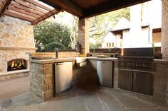 Outdoor kitchen with stainless, BBQ, fridge, and keg! By Outdoor Signature in Argyle, TX