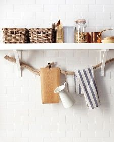 Driftwood, or any other sturdy branch, goes from sculptural to functional when suspended underneath a kitchen shelf. Simply thread it through open wall brackets and use it for dish towels; to hold other lightweight items such as pitchers, pot holders, and cutting boards, try S hooks and loops of thick twine. ♥♥♥!