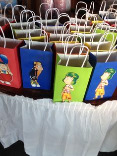 Chavo and friends gift bags. Bought primary color gift bags, I cut out he characters from a El Chavo party plate and hot glued. Tadah!