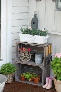Caixote, flores e organização de instrumentos de trabalho no jardim.