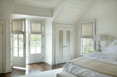 Monochromatic cottage bedroom with white tongue and groove walls and vaulted ceiling. French doors covered with linen roman shades and bi-fold closet doors. White French bed paired with soft white bedding and ivory nightstand with whitewashed wood lamp ... could also be done in soft grays