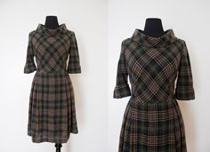 A classic vintage early 1960s day dress.    Light dark brown black and hello plaid wool.  Fitted high rolled neck top with elbow length