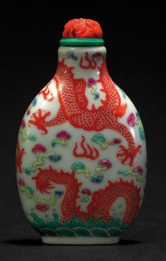 Flacon tabatière en porcelaine décoré en émaux de la famille rose de deux dragons affrontés sur fond de nuages et de vaguelettes à la base. Marque DAOGUANG (1821/1850) au revers en rouge de fer, époque DAOGUANG. Bouchon en corail rouge sculpté. H: 6,7 cm