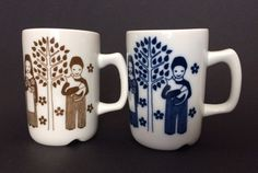 "Pair of mint condition Porsgrund Norwegian coffee mugs. One blue and one brown, girl with flowers, boy holding cat, among trees and sunshine. No chips or cracks, measure 3 1/2"" tall by 2 1/3"" in diameter. 
