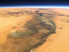 """The Richat Structure, Oudane, Mauritania, is not really a structure but a huge circular formation (50 km in diameter - 30 miles), that resembles an eye when looked upon from space. Originally thought to be a crater, this volcanic dome is most likely a product of erosion. The earliest space missions used it as a landmark. Surprisingly, there is a hotel smack in the middle of the Richat Structure. It's nothing luxurious, but it offers adequate accommodations for """"Mad Max"""" style tourists"""