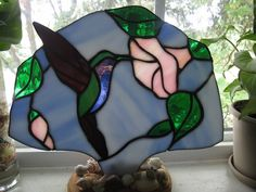 Beautifully Handcrafted Hummingbird on Morning Glory Stained Glass Fan Lamp to brighten up any window or grace any area in your home. Hummingbird is cut from Iridescent glass for the beautifully true look of the feathers. 10 1/2 inches wide and 8 inches tall. A perfect gift for any occasion
