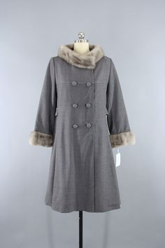 Vintage 1960s winter coat with fur trim. Grey wool twill fabric in a double-breasted cut. Corded fabric buttons, attached back decorative belt, and satin lining. It is in excellent condition. Made of