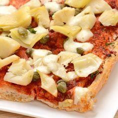 Recept voor een knapperige broodpizza met geurige tomatensaus, artisjokken, kappertjes en gesmolten mozzarella. In amper vijf minuten op tafel! Bak je mee?
