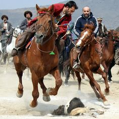 A horseman reaches for the headless carcass of a goat during a game of Buzkashi in Kabul, Afghanistan.