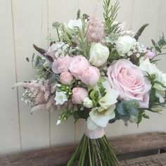 A natural hand tied bridal bouquet of late summer flowers in a palette of pink and Ivory flowers