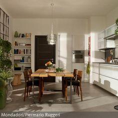 Eine Fusion aus modernem Küchen-Chic und rustikalem Essbereich: Während die…