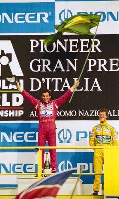 O sorriso de Senna e a bandeira do Brasil em punho se juntam à alegria do jovem Michael Schumacher no pódio do GP da Itália. Em Monza, Senna venceu pela terceira e última vez na difícil temporada da McLaren em 1992. Schumacher foi o terceiro, atrás do companheiro de equipe de Benetton, Martin Brundle