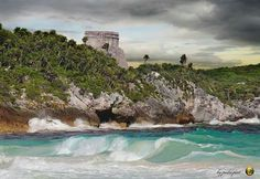 Cloudy sky at noon Hidden by the trees of the jungle emerges majestically on the top of the cliff the main temple of Tulum ,viewed from the shore line of the caribbean sea. Shared by Edith Cruz