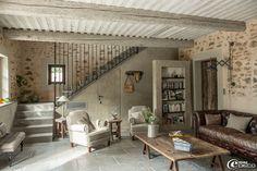 Dans le salon de la maison dhôtes de charme, La Bergerie de Nano, table basse en bois sur tréteaux, canapé en cuir effet vieilli et fauteuils en lin naturel, le tout chez Flamant. Porte en bois sur mesure, Portes Anciennes à Saint-Rémy-de-Provence