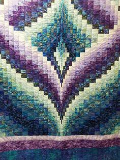 This beautiful queen size Northern Lights features shades of purple and aqua. It measures 96″ x 112″ andis hand quilted by a local Mennonite woman.