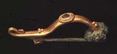 Roman gold fibula 1st-3rd c CE, with granulation and blue glass inlay in a ribbed wire setting. 36mm.