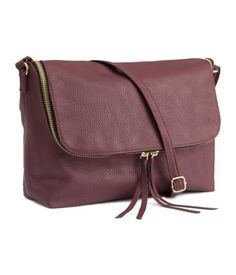 Shoulder bag in imitation leather with a zip around the flap, a narrow, adjustable shoulder strap, and one inner compartment with a zip. Lined. Size 18x28 cm.