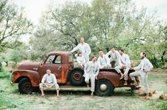 Beautiful bohemian wedding with groomsmen on old antique pick up truck at Vista West Ranch in Dripping Springs, Texas in the Hill Country.