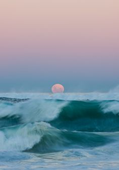 the moon rising above the waves....