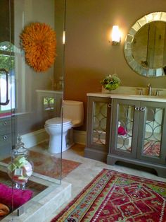 Love that pop of rug color in a neutral bathroom.