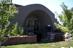 A magnificent concrete archway as one facing of an earth-sheltered home - needs more stonework & logs to make it rustic