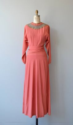 Vintage 1940s coral rayon crepe dress with elaborate brass triangles, brass soutache, tapered sleeves very long wrap around the waist and metal zipper at the back. --- M E A S U R E M E N T S ---  fits like: small bust: 37 waist: 26 hip: 39 length: 57 brand/maker: n/a condition: excellent  ✩ layaway is available for this item  to ensure a good fit, please read the sizing guide: http://www.etsy.com/shop/DearGolden/policy  ✩ layaway is available for this item ...