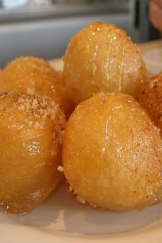 Greek Honey Puffs - Loukoumades Greek Honey Puffs - Loukoumades on BigOven: Loukoumades, one of my favourite Greek pastries, are sweet fritters (similar to doughnuts) that are deep fried till golden brown and served warm with a honey syrup, sprinkled with Greek Sweets, Greek Desserts, Greek Recipes, Just Desserts, Delicious Desserts, Dessert Recipes, Yummy Food, Deep Fried Desserts, Arabic Sweets