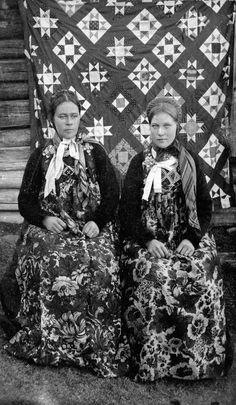 To damer i hallingbunad m. blomstrete forkle, åkle i bakgrunnen