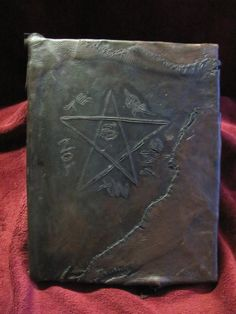 Found in an antique shop in Maine. It is a genuine 'Book of Shadows' used by practitioners of the occult and witchcraft. It is surrounded by deer skin and symbols that have been burned in via gun powder; according to Dr. Barbara DuBois and Dr. David Carrington of Norwich University c.1996. The flesh was sown with common catgut during the 19th century (c. 1800-15). Dates and various occult symbols
