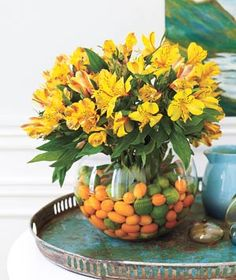 This tone-on-tone assemblage starts with miniature citrus fruits (key limes, kumquats) and Peruvian lilies bursting with color. - 20 Centerpieces for Every Occasion Fishbowl Centerpiece, Fruit Centerpieces, Simple Centerpieces, Centerpiece Ideas, Easter Centerpiece, Centrepieces, Decorating Tips, Decorating Your Home, Glass Fish Bowl
