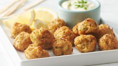 These appetizer bites are a mini way to enjoy crab cakes for your next gathering. Crab, fresh chives and spices are folded into bread crumbs, shaped and baked for the perfect bite. Serve with lemon-garlic sauce for dipping.