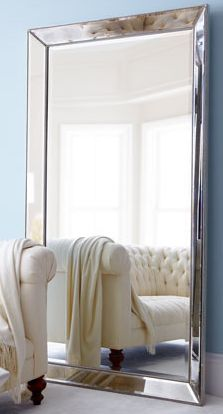 Love the mirror reflecting the tufted sofa. Great idea on how to use tufted tuxedo sofa under the stairway.