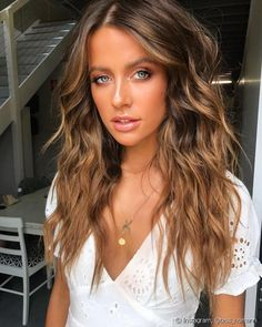 El cabello castaño claro con mechas doradas alrededor del rostro ilumina el rostro