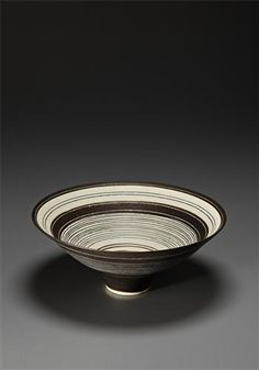 Footed bowl, Porcelain, manganese glaze with concentric circles of sgraffito and inlaid design repeated inside and out. 3 3/8 in. (8.5 cm.) high, 8 3/4 in. (22.3 cm.) diameter, c.1982