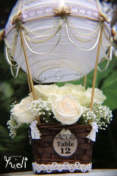 This beautifully handcrafted Hot Air Balloon centerpiece is made using a white paper lantern that has been adorned with high quality ivory and gold ribbon, burlap ribbon, white lace. Decorated with pearl and ivory ribbon draping and embellished with burlap and satin ivory bows. The lantern is attached to a natural brown basket using wooden dowels that are hand painted to match. Each centerpiece will come with a tag with either TABLE NO. or Mr and Mrs. Customization available. ** TWO STYLES…