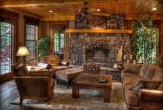 Beautiful log cabin living room with stone fireplace.