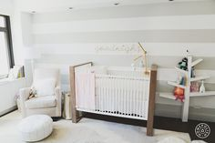 Contemporary nursery features an accent wall painted with white and gray horizontal stripes lined with goodnight light and mobile over a two-tone crib, ducduc Austin Crib, flanked by a light gray velvet glider with white piping, Land of Nod Luca Glider, and white Moroccan leather pouf to the left and a Babyletto Tree Bookcase to the right.