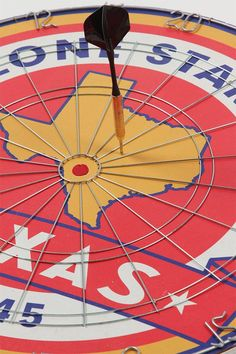 """Every frat house needs a game board! Start a dart tournament or just hang it up and have a blast with the Lone Star State dart board! Challenge all your fraternity brothers! The board is red, white, blue, and yellow with wire rings and numbers. It features """"The Lone Star State 1845"""" around the double ring and has a """"Texas"""" banner underneath the State of Texas shape. The cork board measures 17.5"""" in diameter and is 1"""" thick. Includes 6 traditional brass darts."""