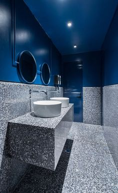 In this modern bathroom, a dark blue paint has been used to create a drama appearance that ties into the blues used throughout the rest of the restaurant. #RestaurantBathroom #BathroomDesign