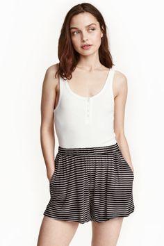 Pantalón corto amplio: Pantalón corto en punto vaporoso con cintura elástica, bolsillos al bies y perneras anchas.