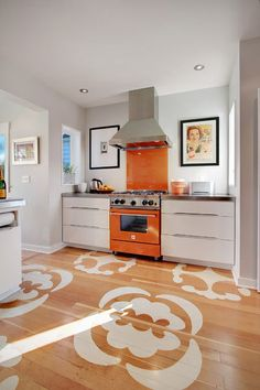 The colors in the framed advertisement next to the stove inspired the bright orange of the new $3,000 Blue Star range and glass-painted backsplash. Fun floor