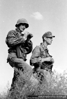 Two Waffen SS glassing enemy positions somewhere on the Eastern Front, summer 1942. Note the camouflage tunics and the camouflage covers for both helmet and soft hat. The Waffen SS was the first German formation to provide its members with universal battlefield camouflage kit.