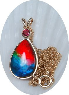A splendid piece of ammolite jewelry--a top  grade tricolour ammolite set in gold with a natural pink sapphire.SOLD