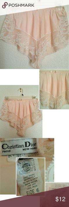 """Vtg. Christian Dior Lingerie Shorts This is a beautiful pair of lingerie tap panty or shorts. Pale pink, trimmed with a wide panel of white lace and a ribbon rosette. Has elasticized waist measuring  12"""" and stretching comfortably to 15"""" across,  14"""" from waist to crotch In very good condition, no holes or stains...see last photo of mild fray at a section on elastic. Content 50% nylon, 27% rayon, 23% polyester. Hand wash separately, line dry. Christian Dior, tag says size 6, most likely fit…"""