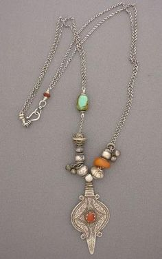 Anne Holland | Necklace made with antique silver beads from Afghanistan, an antique Tibetan bezelled turquoise bead, and an antique Moroccan amber bead, all resting above an antique silver and carnelian Afghani amulet. Tibetans believe that turquoise has strong protective and beneficial medicinal properties, and that it is a living thing, not just a simple stone. On a sterling silver chain, with a sterling silver hook and eye clasp. | Dorje Designs by lilia